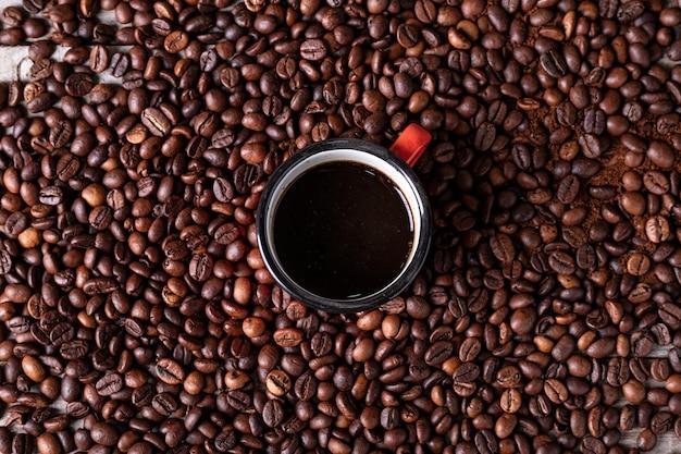 作りたてのコーヒーを中心に赤い金属製のカップとコーヒー豆 Premium写真