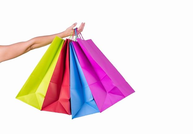 女性の手が分離されたカラーペーパーバッグを保持します。 Premium写真