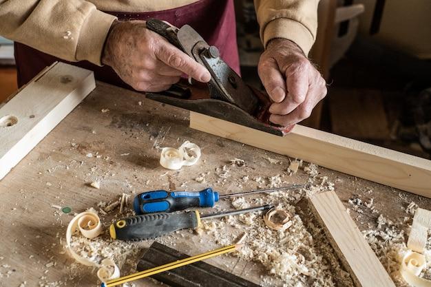 Человек плотника выскабливая завитые деревянные отходы с ручным плоским инструментом и деревянной доской. Premium Фотографии