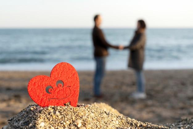 恋人のカップルと海沿いの砂の山に赤いハート。サンバレンタインの概念 Premium写真