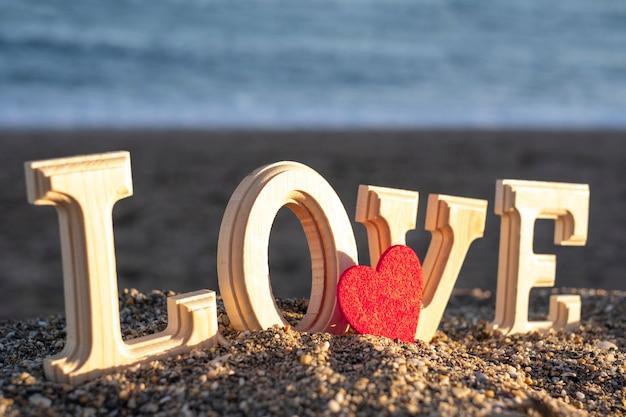 海岸に赤いハートと愛という言葉を形成する木製の手紙。恋人たちの概念 Premium写真