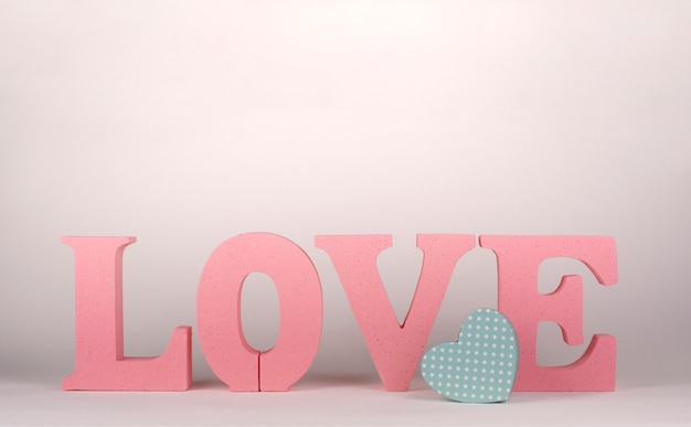 Слово любовь с розовыми пробковыми буквами и небольшой картонной коробкой в форме сердца. день святого валентина Premium Фотографии