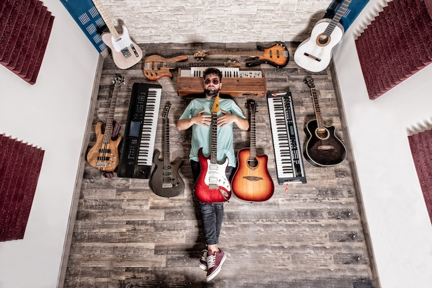 ギターとピアノの音楽スタジオで横になっているミュージシャン Premium写真