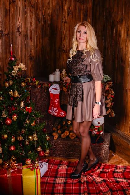 美しい幸せな女がクリスマスツリーとポーズします。クリスマスの時期。 Premium写真