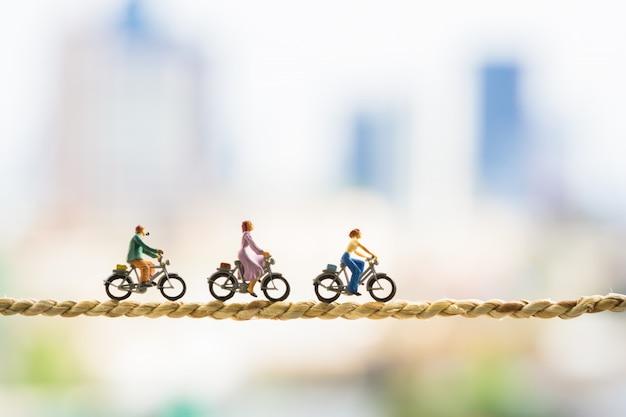 都市の背景を持つロープに小さなサイクリングフィギュア。 Premium写真
