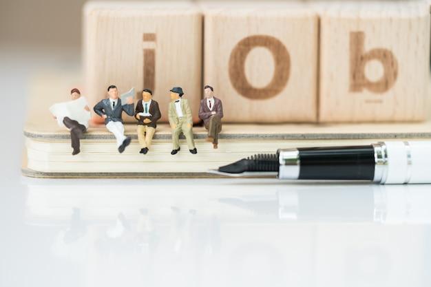木製のブロックからペンと仕事の言葉でノートに座って事業チームのグループ。 Premium写真