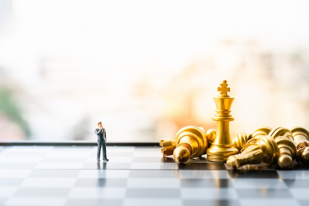 小さなビジネスマン図立っているとチェスの駒とチェス盤の上を歩きます。 Premium写真