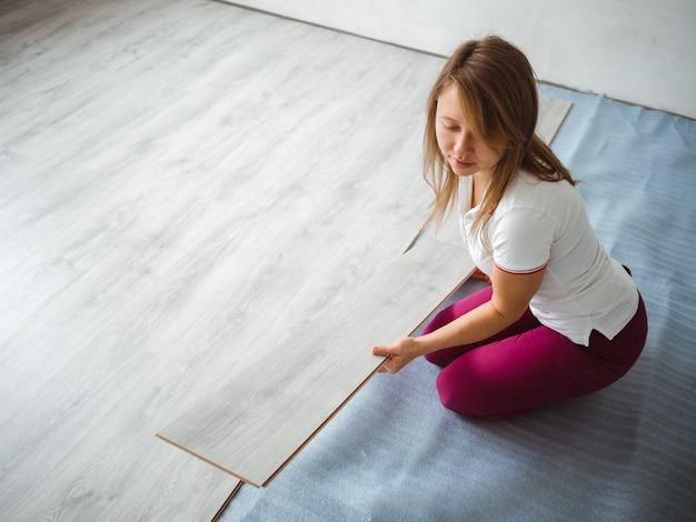 アパートの修理プロセス。積層板を保持している女の子 Premium写真