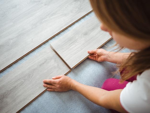 アパートの修理プロセス。女の子はラミネートを床に置きます。背面図 Premium写真