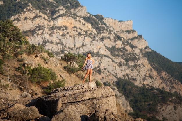 ビーチで高い石の上の少女 Premium写真