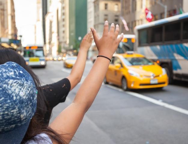 Туристы называют желтое такси на манхэттене типичным жестом Premium Фотографии