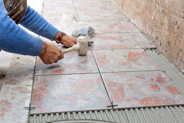 タイル張りの床で作業する瓦職人 Premium写真