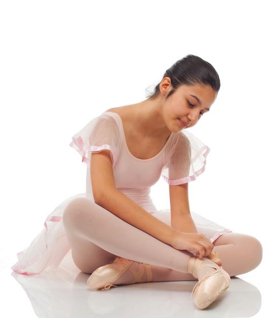 ダンスのために彼の靴を結ぶ間バレリーナ。 Premium写真