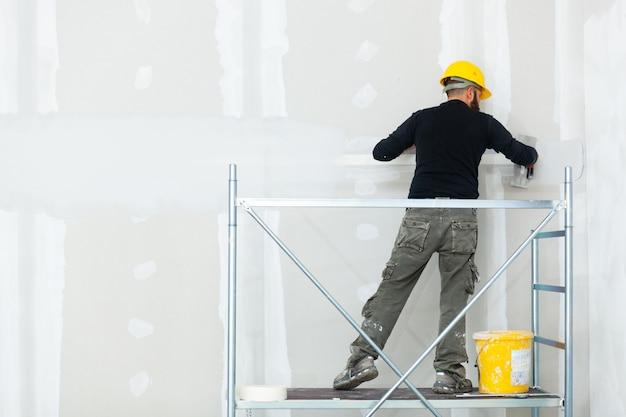 石膏ボードの壁を左官工事労働者。 Premium写真
