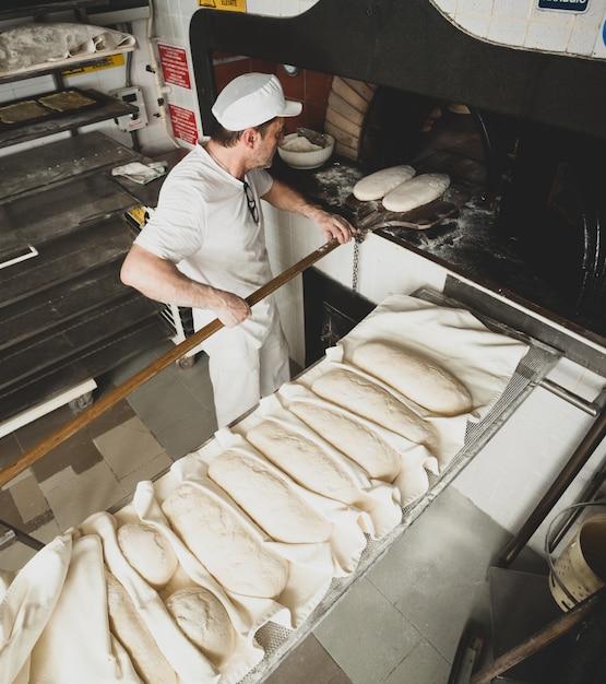 ベーカリーでの木製オーブンによる焼きたてのパンの製造。 Premium写真