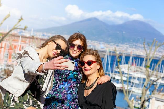 Трое туристов делают селфи перед везувио. Premium Фотографии