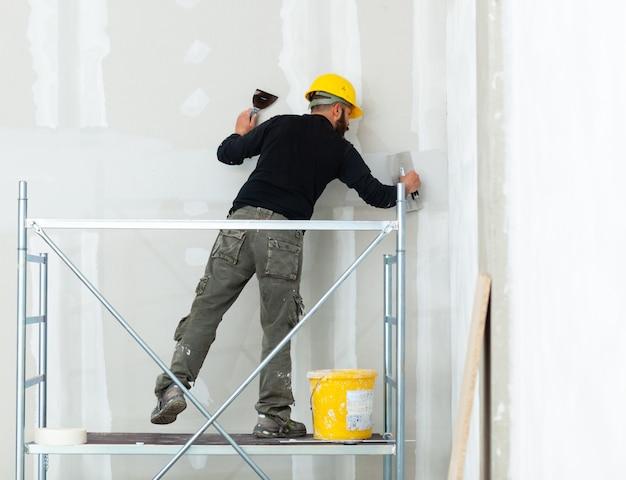 石膏ボード壁を左官工事労働者。 Premium写真