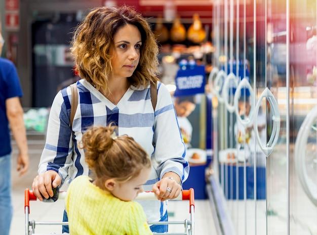 母と娘のスーパーで食料品の買い物 Premium写真