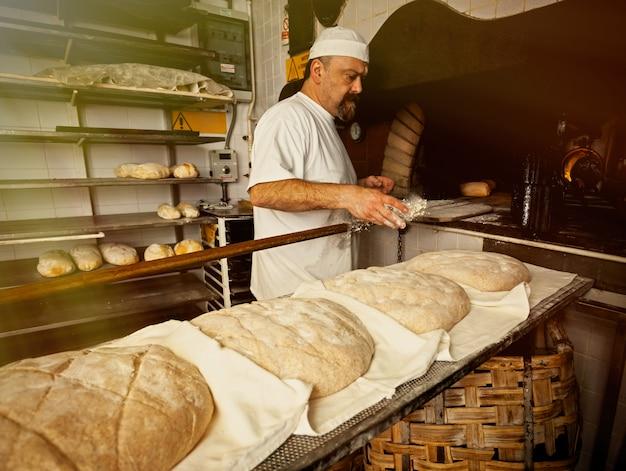 ベーカリーでの木製オーブンによる焼きたてのパンの製造 Premium写真