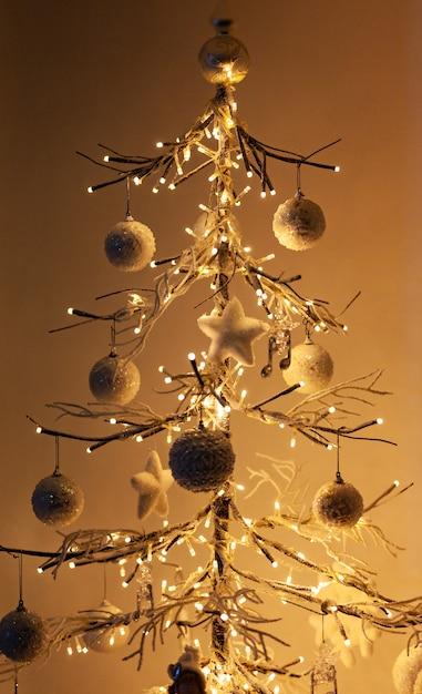 暖かい光と影の白い壁の前に立っている最小限のクリスマスツリー Premium写真