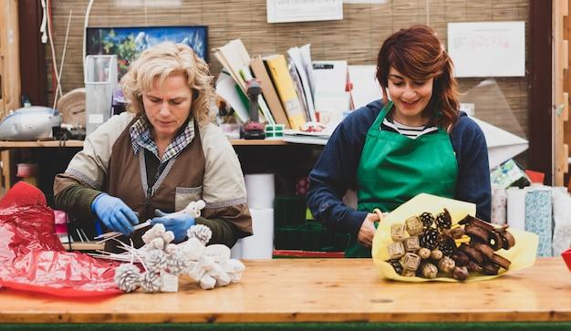 Флористы работают в питомнике. Premium Фотографии