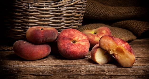 Пончик персик на деревенский деревянный столик. Premium Фотографии