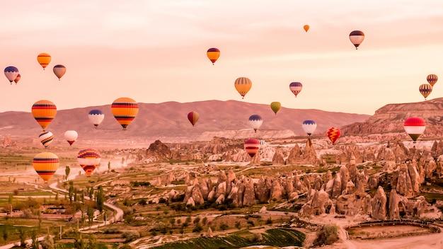 Красочные воздушные шары пролетели над скалой в каппадокии турции Premium Фотографии