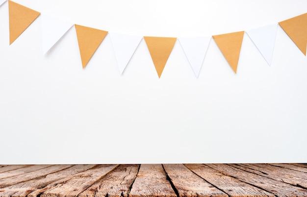 Деревянный стол и висящие бумажные флаги на фоне белой стены Premium Фотографии