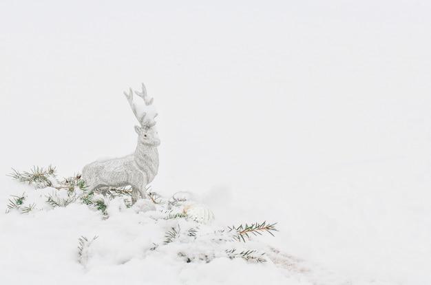 白い雪でシルバーグレーの光沢のあるクリスマスのトナカイ Premium写真
