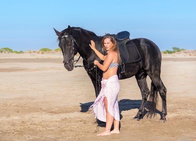 Лошадь женщина на пляже Premium Фотографии