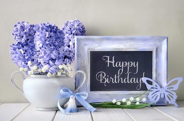 Синие украшения и гиацинт цветы на белом столе, доска с текстом Premium Фотографии