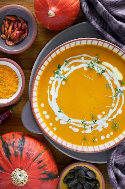 Тыквенный крем-суп в керамической миске с добавлением ростков сливок и кресс-салата на дереве Premium Фотографии