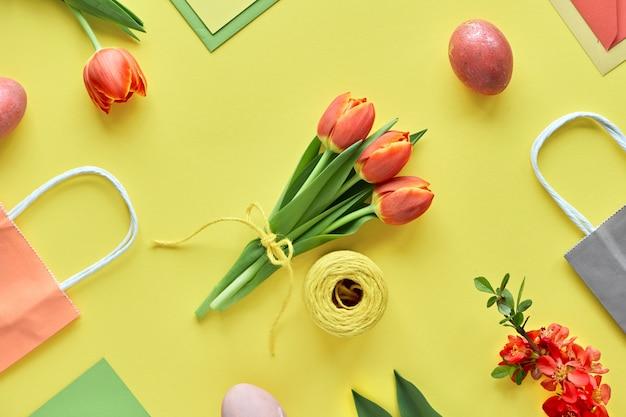イースターフラットは黄色い紙に横たわっていた。チューリップの束、ギフトボックス、装飾的な卵と紙袋、幾何学的な配置 Premium写真