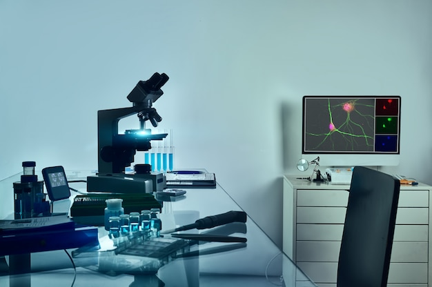 顕微鏡、神経細胞のデジタル蛍光画像とコンピューターテーブル、ガラステーブル上の組織学的固定ツール。 Premium写真