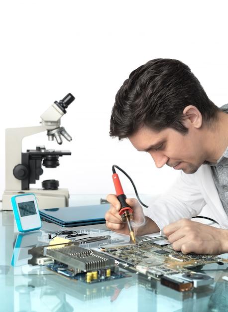 若いエネルギッシュな男性技術者またはエンジニアが電子機器を修理 Premium写真