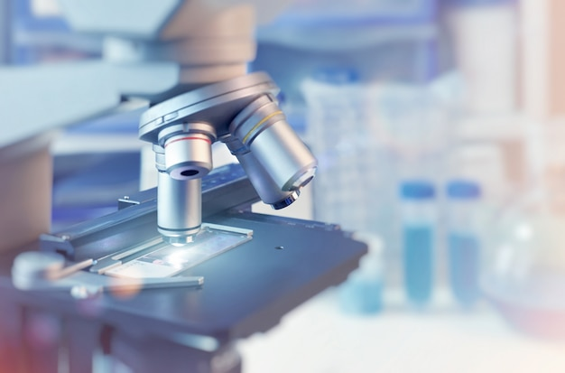 Научный с крупным планом на световом микроскопе и размытой лаборатории Premium Фотографии