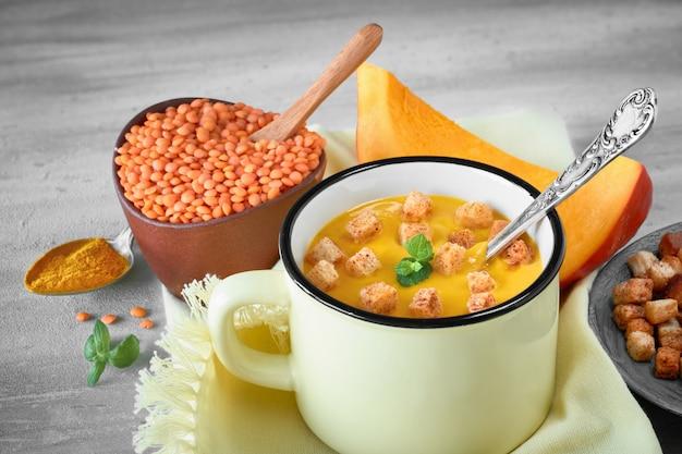 おいしいナプキンに明るい黄色のマグカップでクルトンを添えたおいしいパンプキンクリームスープ Premium写真