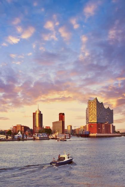 Лодка с туристами идет к эльбфилармонии в гамбурге на закате Premium Фотографии