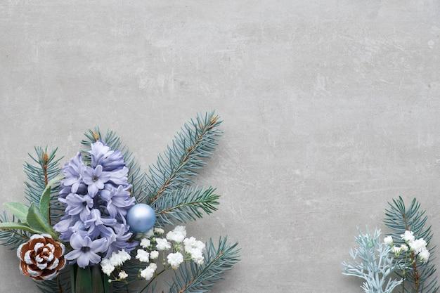 Зимний цветочный уголок зеленого и синего цвета с еловыми ветками, цветами гиацинта и листьями на бетонном фоне Premium Фотографии