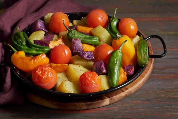 素朴なオーブン焼き野菜のグラタン皿。リネンタオルで暗い木製のテーブルに季節のベジタリアンビーガン食事。 Premium写真