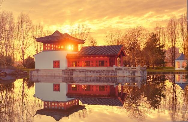 池に映る装飾的なパビリオンと正式な中国の庭の冬景色 Premium写真