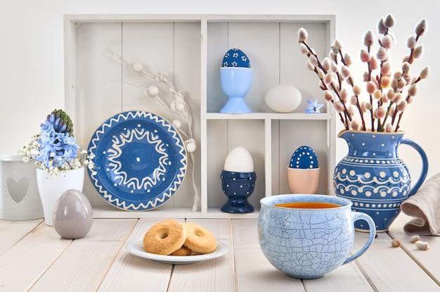 ネコヤナギと春の装飾の束と白いテーブルの上のコーヒーとクッキーのカップ Premium写真