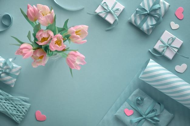 ピンクのチューリップ、縞模様の包装紙、ギフトボックスと青色の背景 Premium写真
