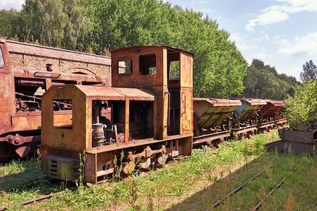 歴史的なレンガ工場の遺棄された錆びた蒸気機関車と石炭車 Premium写真