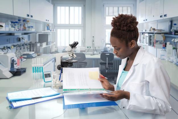 アフリカ系アメリカ人の科学者が研究施設で実験室ジャーナルを読む Premium写真