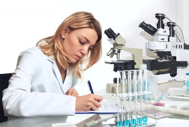 若い女性科学者または技術者が進捗報告書を書き留める Premium写真