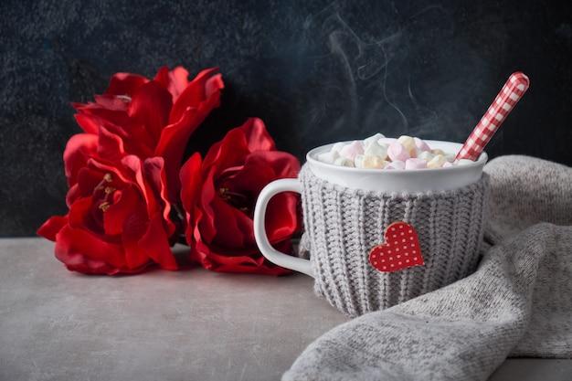 マシュマロ、冬の装飾とテーブルの上のカップに赤いハートのホットチョコレート Premium写真