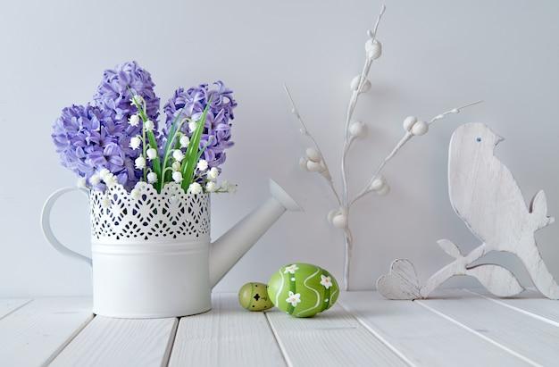 青いヒヤシンスとスズランの花、木の心、鳥、緑のイースターエッグ Premium写真