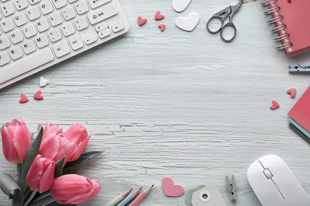 Весенняя плоская планировка с клавиатурой, мышью, розовыми тюльпанами, канцелярскими принадлежностями, открытками, декоративными сердечками и копией пространства Premium Фотографии