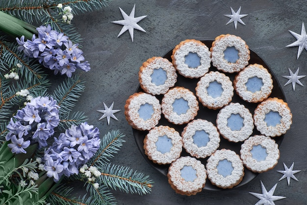 暗い冬に青いガラスと花リンツァークッキーのトップビュー Premium写真